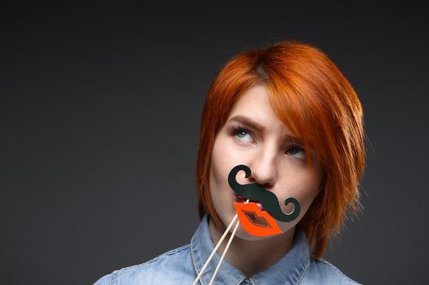 面白い赤毛の女性は偽の口ひげと唇を着用します