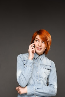 Рыжая женщина разговаривает по мобильному телефону
