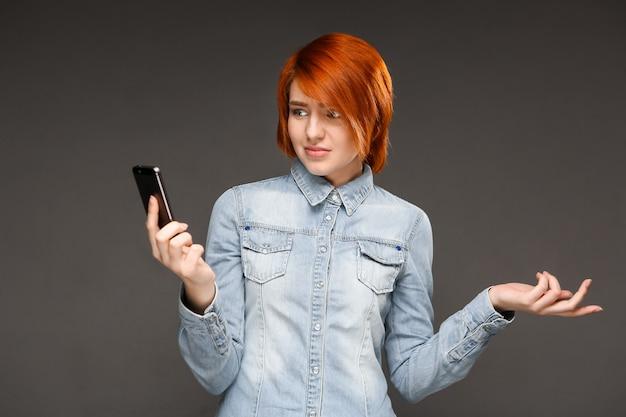 Рыжая женщина смущенно смотрит на мобильный телефон