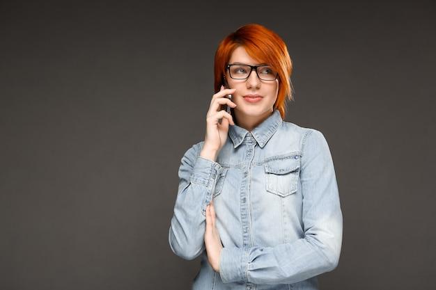 携帯電話で話している赤毛の女性