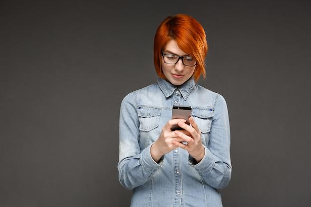 Рыжая женщина текстовых сообщений мобильного телефона, обмен сообщениями