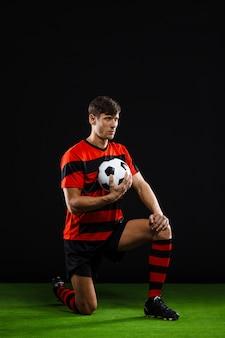 Футболист с мячом стоит на коленях, играет в футбол