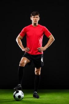ボールを持って立って、サッカーをするサッカー選手
