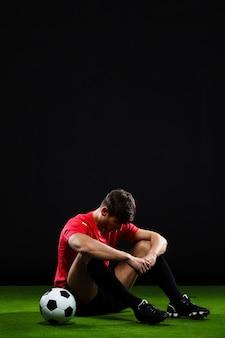 Футболист сидит с мячом на траве, проиграл матч