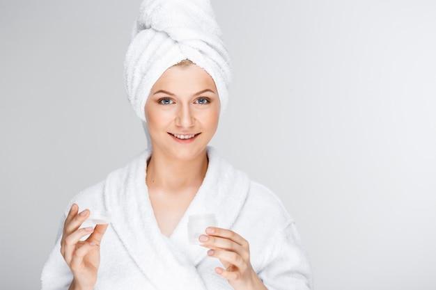 クリームを示す髪にバスタオルで優しい金髪の女性