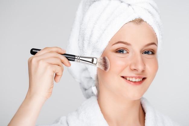 幸せなきれいな女性がブラシで化粧を適用、バスタオルを着用