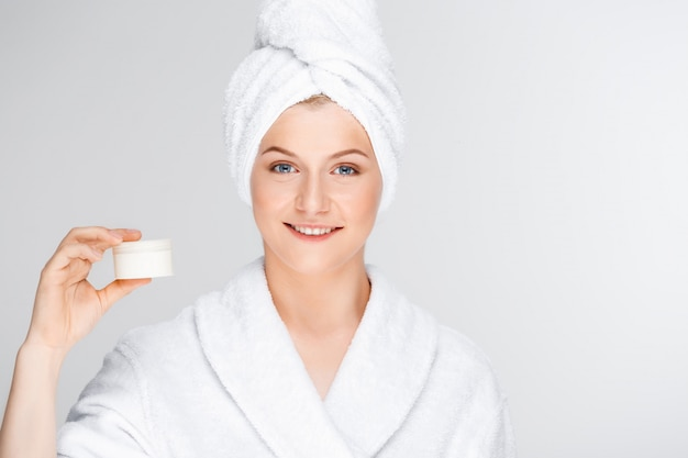 クリーム、スキンケア製品のプロモーションを示すバスローブの女性