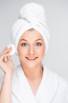 若い女性はシャワーでスキンケアルーチンを行う