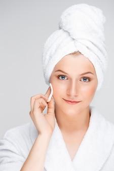 若い女性の化粧後の顔のクレンジング