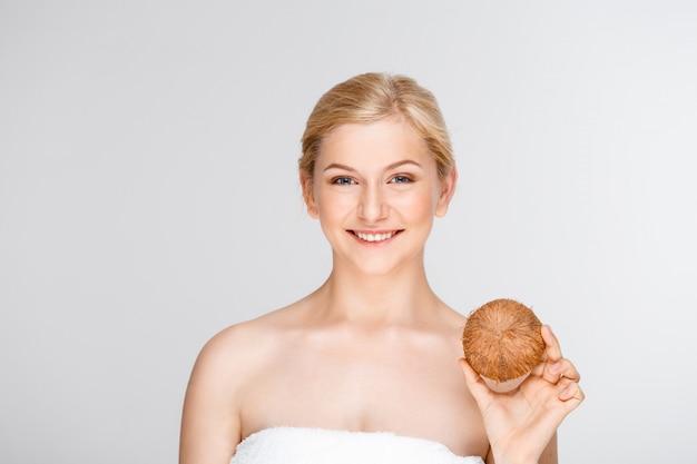 Красивая усмехаясь женщина в курорте держа кокос