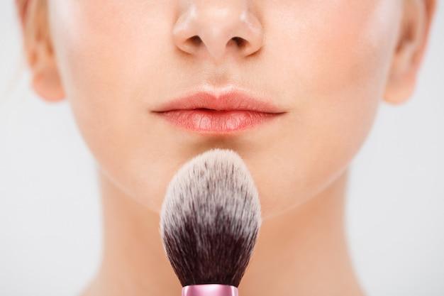 女性のあごと唇、ブラシで化粧をする