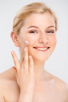 美しい笑顔の女性は、顔のクリームを適用します