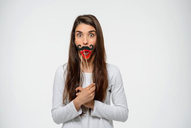 偽の唇と口ひげを持つ面白がってかわいい女性