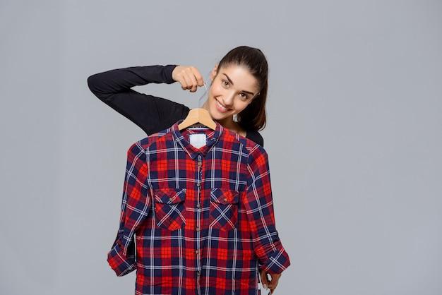 シャツを保持している服を選ぶ女性