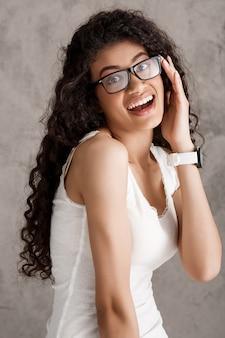 Красивая кудрявая испанская женщина в очках, улыбаясь