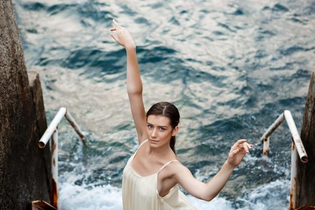 Молодая красивая балерина танцует и позирует снаружи, морская стена