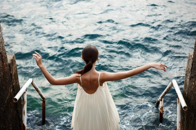 若い美しいバレリーナダンスとポーズ、外、海の壁