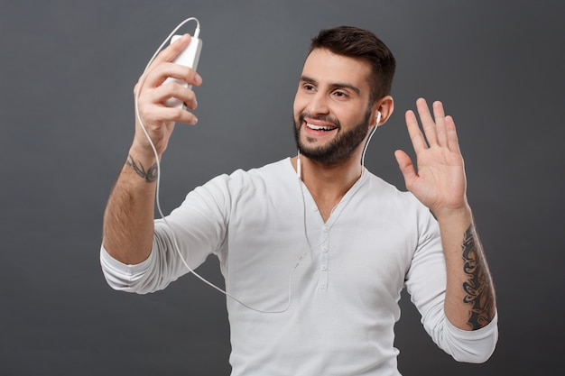 Молодой человек улыбается, глядя на телефон приветствие на серую стену