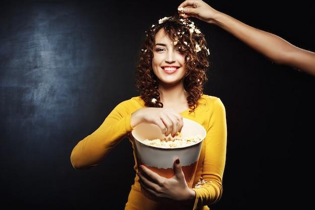 Подруга тушит попкорн на красивой женщине во время просмотра интересного фильма