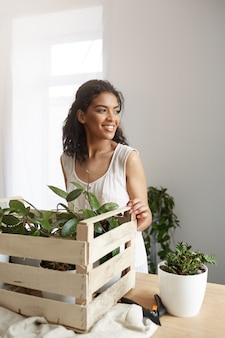 Работа красивой женщины усмехаясь с заводами в коробке на рабочем месте белая стена.