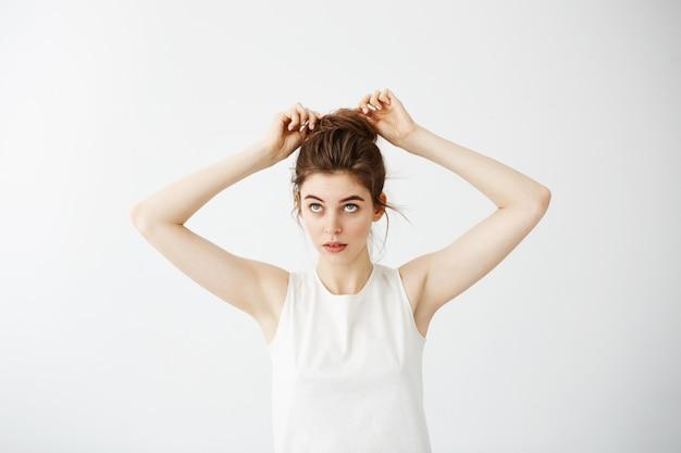 髪のパンを修正する若い美しい女性