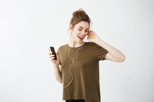 ヘッドフォンで音楽を聴いて幸せな陽気な若い女性