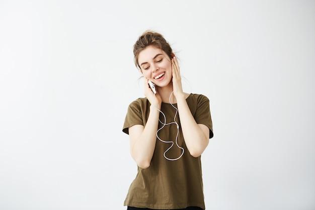 夢のような若い美しい女性のヘッドフォンで音楽を聴く笑顔