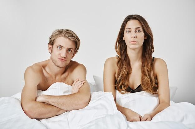 毛布の下のベッドに座って満足していない失望したカップル、ボーイフレンドは混乱の中で手を交差します。