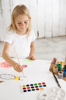 Игривая, очаровательная маленькая белокурая девушка с веснушками в белой ткани рисует облака и цветы на белом листе бумаги