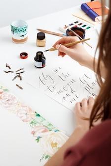 Женщина пишет каллиграфию на открытках