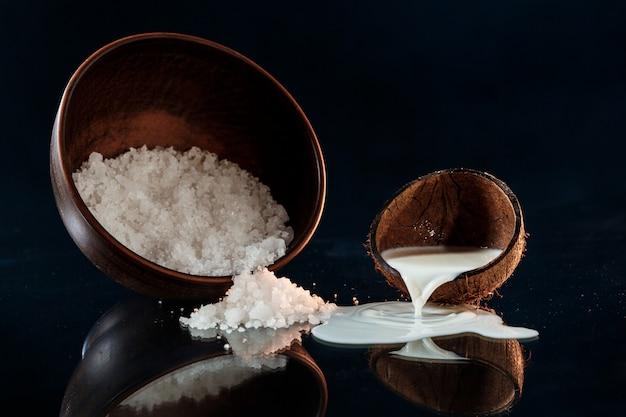 木製のボウルに海の塩と黒の表面にココナッツ