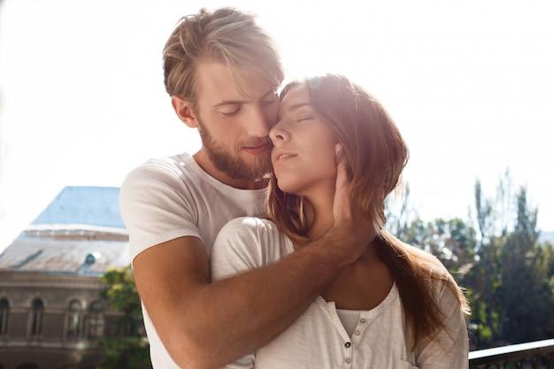 Молодая красивая пара, улыбаясь, наслаждаясь стоя на балконе
