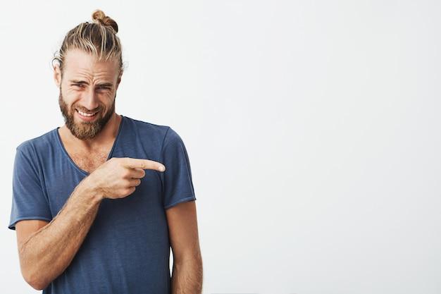 白い壁を指してトレンディなヘアスタイルで魅力的なひげを生やした男の肖像画を間近します。