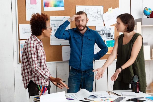同僚は、図面、オフィスでの新しいアイデアについて議論、議論している