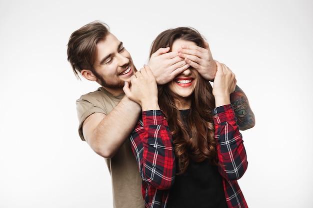彼女の驚きに女性の目を覆っている男