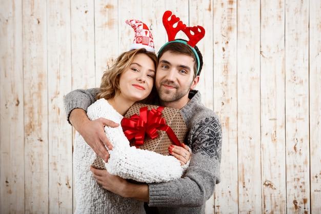 Молодая пара улыбается, обнимая, держа рождественский подарок на деревянные поверхности