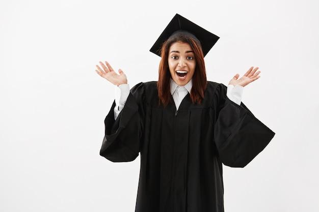 Счастливый удивленный выпускник женщины показывать смотрящ камеру над белой поверхностью