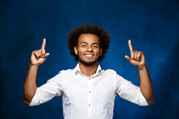 青い表面上に指を上向きの若いハンサムな男