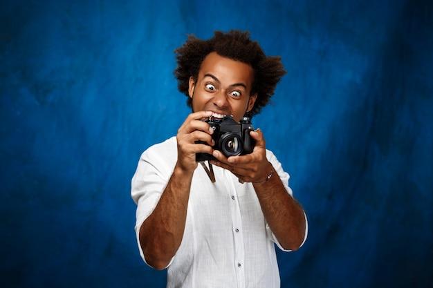 青い表面上の古いカメラを保持している若いハンサムな男