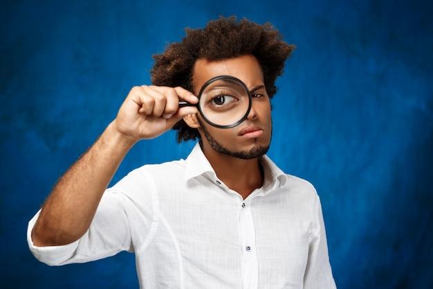 青い表面上の拡大鏡でポーズ若いハンサムな男