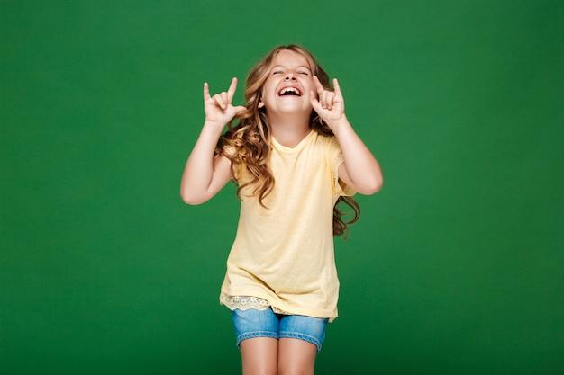 緑の壁で笑っている若いきれいな女の子