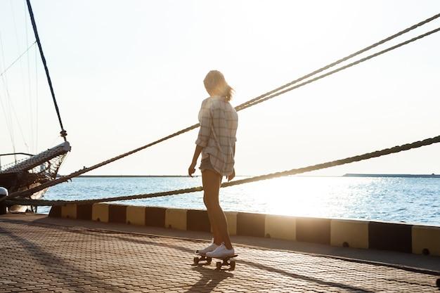 海辺を歩いて、スケートボードの若い美しい女性