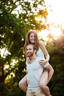 休んで、公園を歩いて、笑みを浮かべて、屋外の喜びの若い美しいカップル