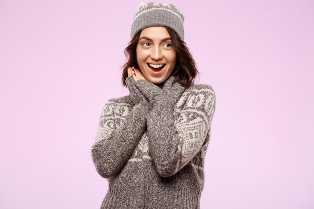 Счастливая молодая красивая женщина брюнет усмехаясь над светлой стеной