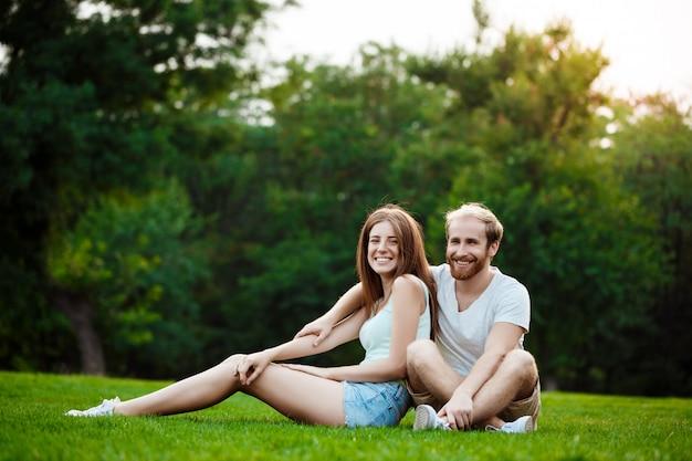 笑みを浮かべて、公園の芝生の上に座っている若い美しいカップル