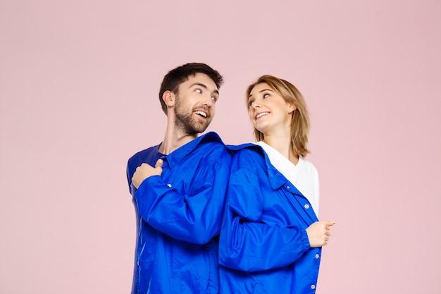Смешная молодая красивая пара в пиджаке на светло-розовой стене