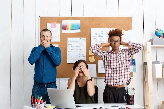 同僚がオフィスで手で口、目、耳を閉じている耳を傾けて話す邪悪な変化はありません。