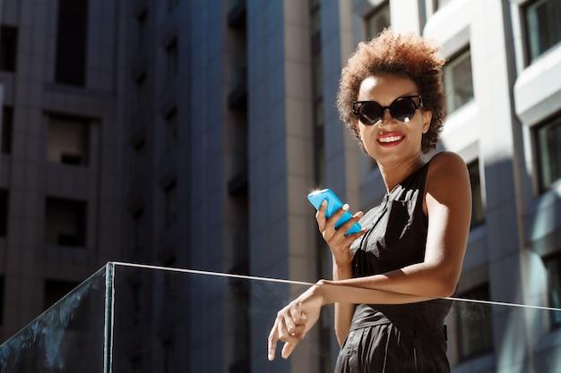 街を歩いて持株電話を笑顔若い美しい女性