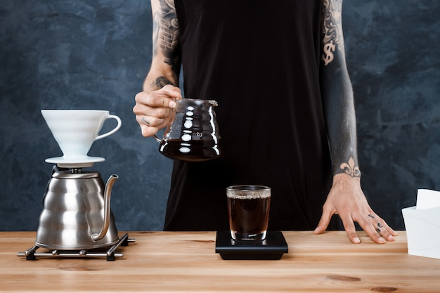 Мужской бариста, заваривающий кофе