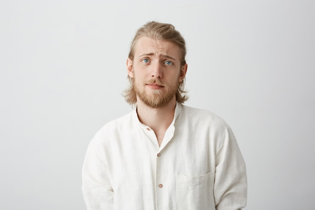 Красивый бородатый кавказский мужчина со светлыми волосами, поднимающими брови, выглядит очень мило и мрачно, как будто просит милости или просит совета
